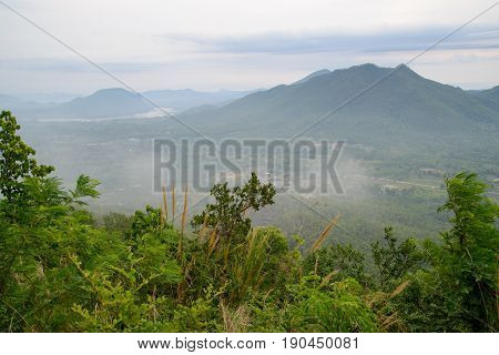 Wide angle view of wispy morning fog in front of a mountain valley with foliage and trees in the foreground. Phu Thok Loei Thailand. Travel and environment concept.