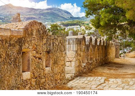 Inner courtyard & fortifications surrounded by stone walls Fortezza Castle - Venetian fortress with Bastion defense system on hill Paleokastro in resort Rethymno. Historical attractions Crete Greece