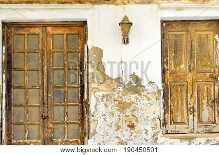 Old concrete wall with two dusty wooden doors. Resort classic Greek architecture in port city Rethymno Crete Greece