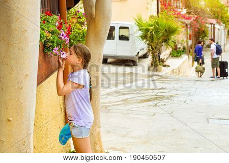 Cute teenage girl sniffing flowers growing in a flower bed on narrow cobbled street. Tourists walk on city touristic trails. Resort classic Greek architecture in port city Rethymno Crete Greece