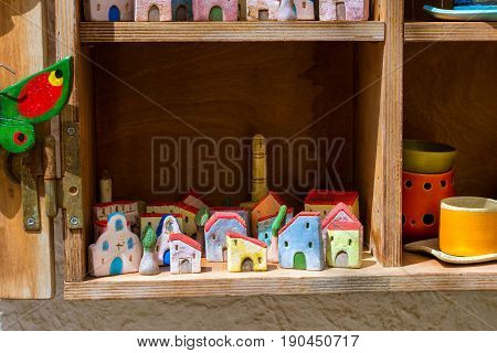 Handmade souvenir clay houses in window of tourist resort store. Resort classic Greek architecture in port-city Rethymno. Rethymno, Crete, Greece