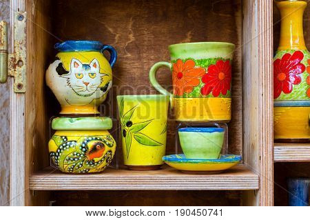 Handmade souvenir ceramic mugs in window of tourist resort store. Resort classic Greek sculpture in port-city Rethymno. Crete Greece. Rethymno