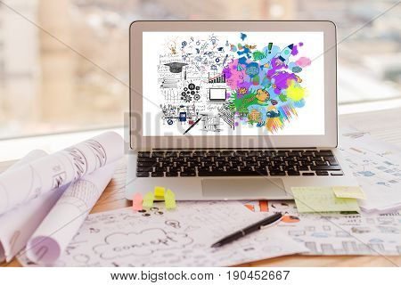 Laptop with sketch on screen placed on messy workplace. Left and right brain sides concept