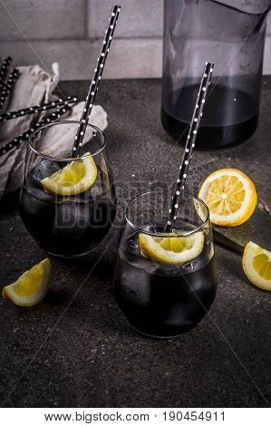 Trendy food. Summer refreshment drinks. Detox and diet concept. Black lemonade with charcoal ice lemon juice and lemon. On a home stone table with black straws for drinking. Copy space