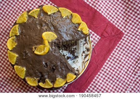 top view of a cake with melted chocolate and oranges