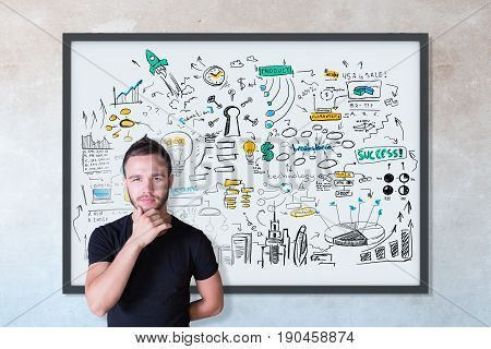 Thoughtful young male with business sketch in frame on concrete wall background. Achievement concept