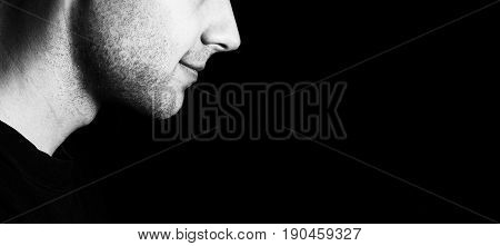 Profile of a guy with a bristles smiling on a black background low key