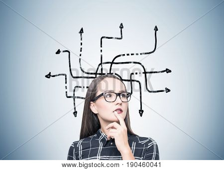 Portrait of a nerdy girl in glasses standing near a gray wall with an arrow maze. Ways lead to different directions. Concept of choice