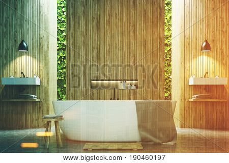 Eco bathroom interior with two narrow windows green shrubbery is seen through them. There are two sinks by the sides of a white tub standing near a wooden wall. 3d rendering mock up toned image