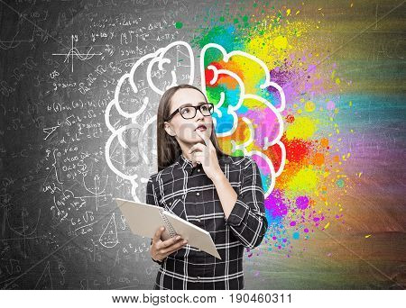 Portrait of a geek girl in glasses standing near a blackboard with a copybook and a big colorful brain with with formulas around it.