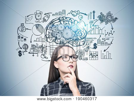 Portrait of a geek girl in glasses standing near a gray wall with a copybook and a brain with gears on top of it. Toned image