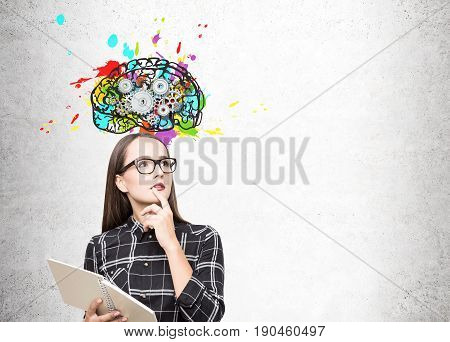 Portrait of a geek girl in glasses standing near a concrete wall with a copybook and a colorful brain with gears on top of it. Mock up