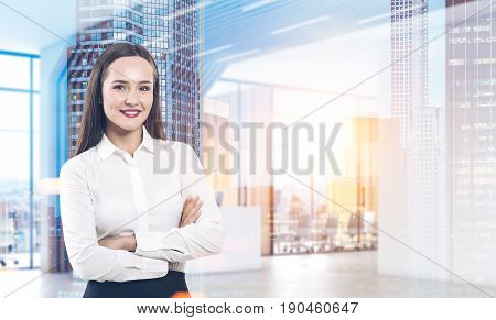 Portrait of a cheerful young businesswoman standing with crossed arms and looking at you. She is standing in a modern office lobby with a cityscape. Mock up toned image double exposure.