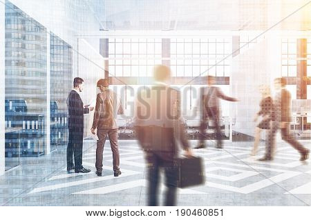 Business people near office cubicles in an office with white and wooden walls. There are blank vertical pictures in each of them a desk with a computer a chair and shelves. Side view. 3d rendering