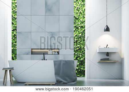 Eco bathroom interior with two narrow windows green shrubbery is seen through them. There are two sinks by the sides of a white tub standing near a marble tile wall. Close up. 3d rendering mock up