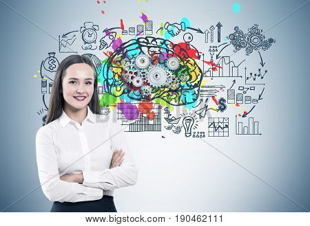 Portrait of a young smiling businesswoman standing with crossed arms near a gray wall with a colorful brain sketch cogs on top of it and a business scheme