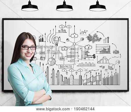 Young businesswoman wearing glasses and a blueish shirt standing with crossed arms and smiling. Whiteboard with a business scheme