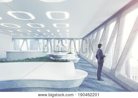 Side view of a man in glasses standing near a panoramic office window with a cup of coffee. There are futuristic flower beds a curved reception table and oval flower lamps. 3d rendering toned image