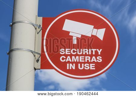 Red Security Camera In Use Sign on Gray Post and Mostly Sunny Background V