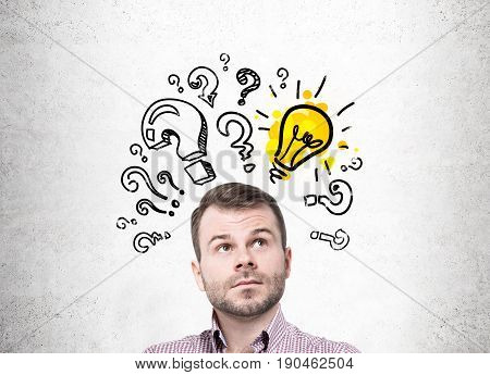 Pensive bearded young man standing near a concrete wall looking upwards. There is a yellow light bulb sketch surrounded by question marks