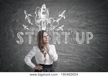 Portrait of a young charming businesswoman wearing a white blouse and a black skirt. Her light colored hair is braided. She is thinking. Blackboard background with a startup rocket