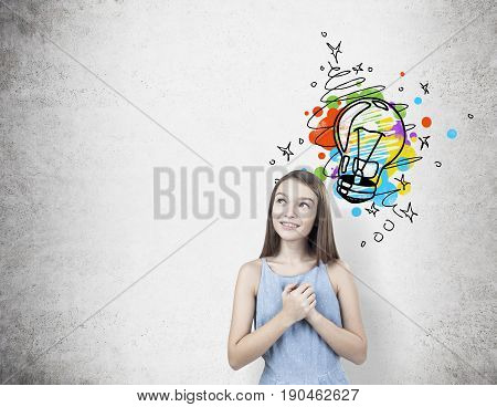 Portrait of a dreamy teen girl wearing a blue dress and standing with her hands near the heart and looking upwards near a concrete wall with a colorful light bulb. Mock up