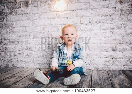 A Stylish Child, A Boy, One Year Old, Sit On A Wooden Floor And On A Brick Wall Background. He Is Dr