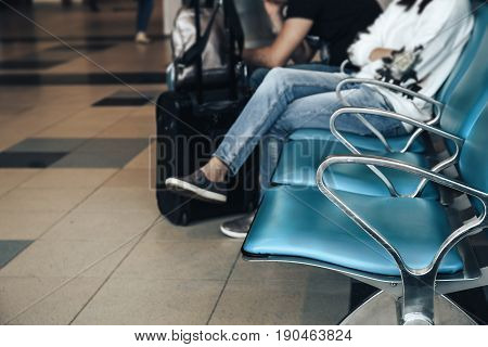 Airport waiting area, row of chairs, blurred people travellers wait for the flight in airport, departure terminal
