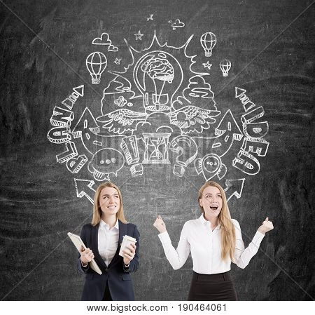 Portrait of businesswomen twins. One is holding a coffee and a notebook. The second is really happy. They stand near a blackboard with a round idea sketch