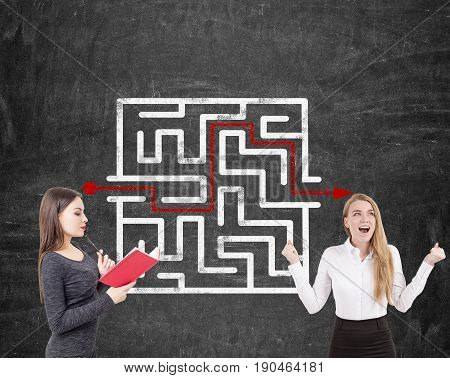 Portrait of two businesswomen. One is wearing a dress and reading a book. The second is screaming with joy. They are standing near a blackboard with a labyrinth sketch on it.