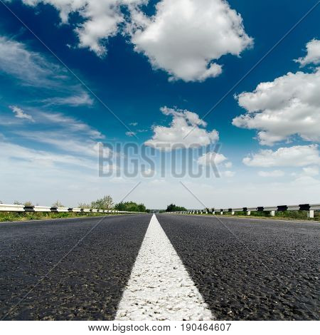 asphalt road closeup with white line on center and low dramatic clouds in blue sky