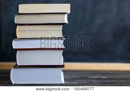 School concept. Back to school concept. Stack of books close up on wooden desk with chalkboard as background