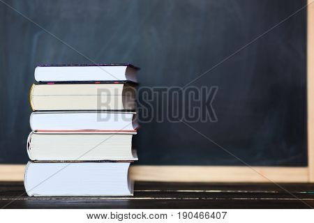 School education concept. Stack of book close up on wooden desk with school chalkboard as background