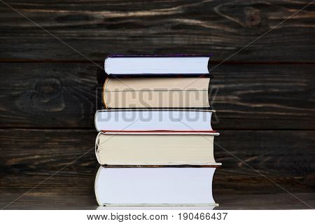 School concept. Back to school concept. Stack of book close up on table with brown wooden background.