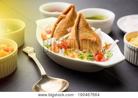 popular indian snack called Dahi Samosa or samosa dipped in curd, favourite tea time junk food or snack served with tamarind and mint chutney or tomato ketchup and green fried chilli and sev/bhujiya
