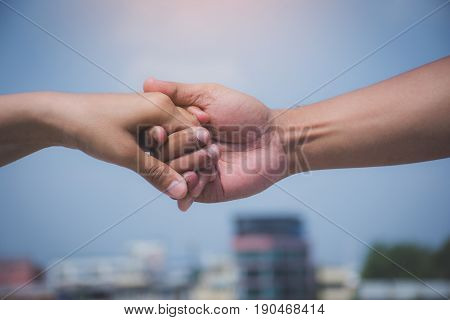 Friendship and love concept between man and woman - man's hand hold by a girl hand isolated on the blue background