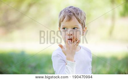 Cute little boy licking fingers while eating chocolate outdoors