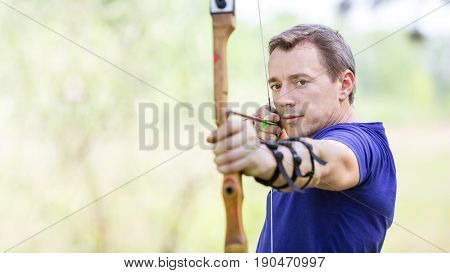 Bowman aiming arrow at target image with selective focus
