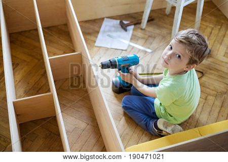 Young boy with screwdriver looking up while sitting on floor at unfinished shelf unit or bookcase