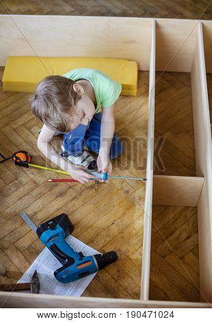 Cute young boy using screwdriver while sitting on floor at unfinished shelf unit or bookcase view from above