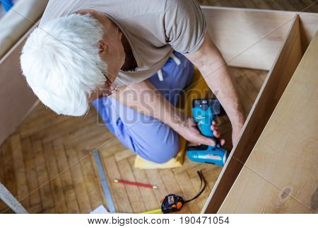 Mature man using electric screwdriver while making bookcase or shelf unit view from above