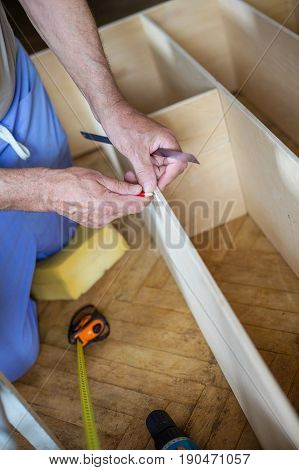Mature man measuring wooden shelf with measure tape and making marks with pencil while assembling bookcase or shelf unit view from above