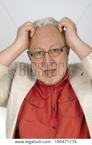 White haired senior with glasses tearing his hair - on bright background