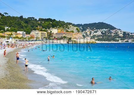 NICE, FRANCE - JUNE 4, 2017: People on the beach in Nice, in the French Riviera, France, next to the Promenade des Anglais, the famous seafront walkway of the city