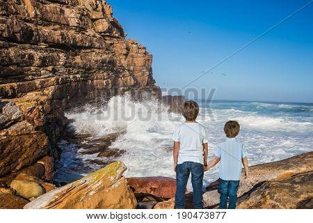 The concept of active tourism and recreation. Travel to South Africa. Two boys standing  on Cape of Good Hope - the south-western point of Africa