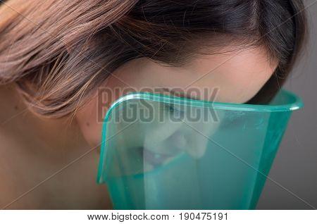 Close up of a beautiful woman doing inhalation with a vaporizer nebulizer machine on black background.