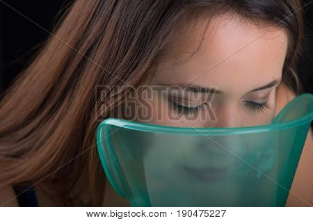 Young woman doing inhalation with a medical vaporizer nebulizer machine on black background.