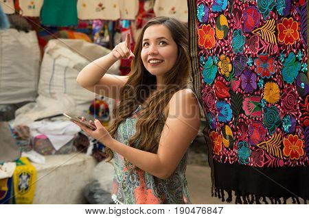 Beautiful smiling young woman holding her celphone with one hand and pointing somewhere with her other hand, andean traditional clothing textile yarn and woven by hand in wool, colorful fabrics background.