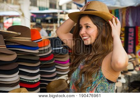 Beautiful woman wearing a handmade Panama Hat at the craft market in Otavalo, Ecuador, colorful fabrics background.