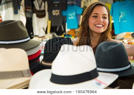 Beautiful woman looking a handmade Panama Hat at the craft market in Otavalo, Ecuador, colorful fabrics background.